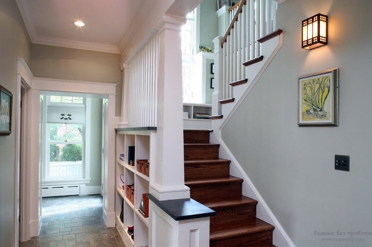 Дизайн белого интерьера с лестницей в прихожей визуально делает пространство более светлым