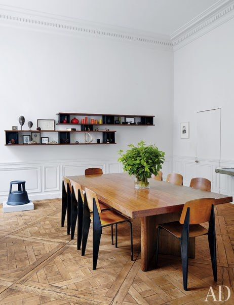 Prouvé Standard school chairs surround the dining room's Jeanneret conference table; the shelves are by Perriand/Prouvé, and the parquet de Versailles floor is 18th century.