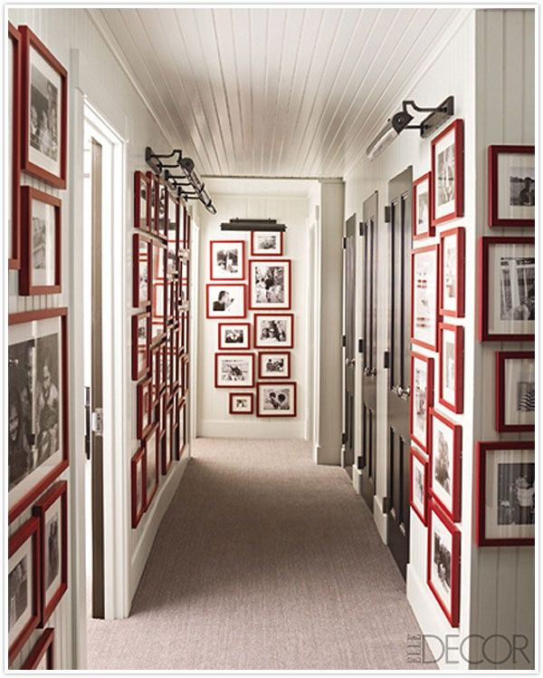 photos on wall---all black and white in same color frame, lining hallway.  nice that the ceiling is beadboard, also