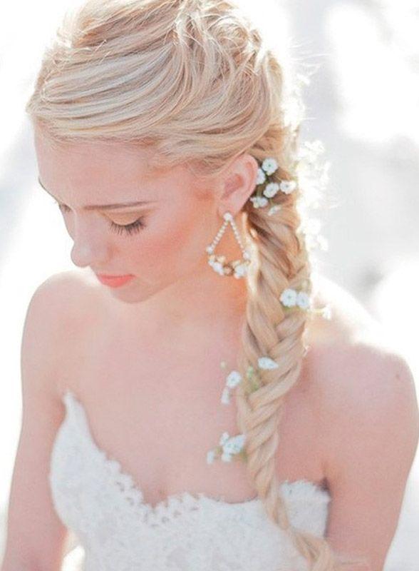 Acconciatura sposa con morbida treccia addobbata con fiori sparsi
