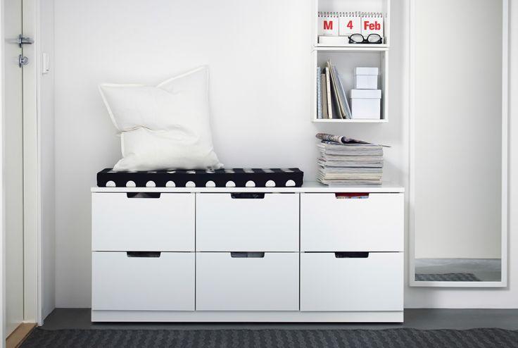 Arcón con colchoncillo de IKEA. Espejo de cuerpo entero y almacenaje abierto en la pared.