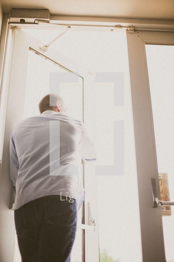 man opening doors. a second chances awaits.