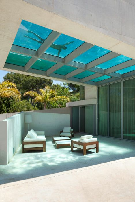 A rooftop swimming pool with a glass floor cantilevers out beside the entrance to this house in Marbella, Spain