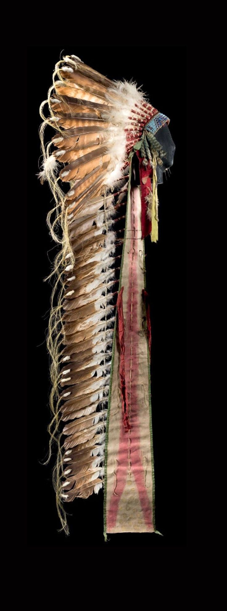 Warrior's headdress; Plains Indians; possibly Sioux   Eagle feathers, red felt, cloth, glass beads, wool and fur   ca. 1910  
