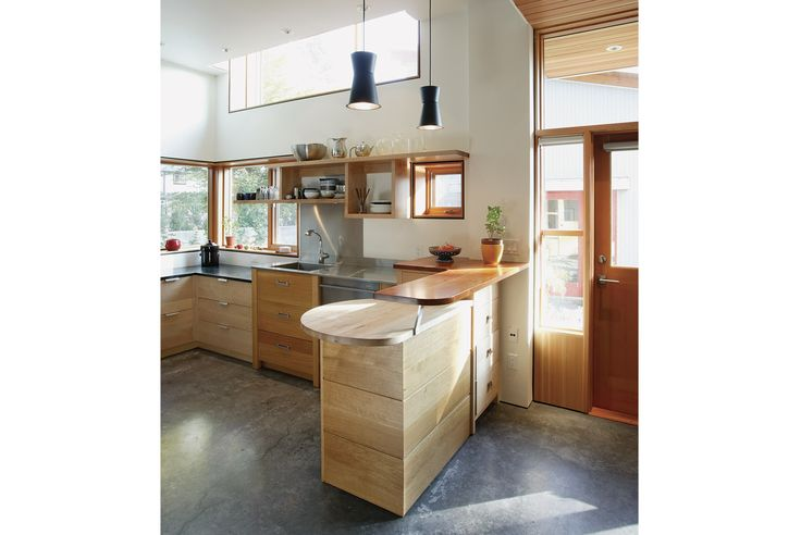 The kitchen is partially defined by a tiered peninsula set under two matte-black Sentry pendant lights.