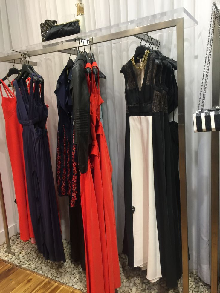 at the side of group of mannequins that wear the long dress, those type of dress hang up. each part of merchandising have a theme. hang up those dresses can show people carefully how  the dress looks like. and they also put some accessories beside.