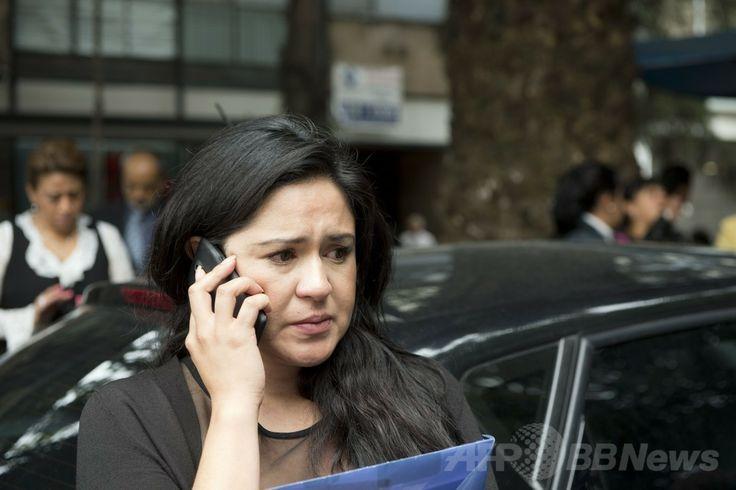メキシコの首都メキシコ市(Mexico City)で、地震の発生後に電話を掛ける女性(2014年5月8日撮影)。(c)AFP/Yuri CORTEZ ▼9May2014AFP メキシコ南部でM6.4の地震、道路橋が倒壊 http://www.afpbb.com/articles/-/3014459