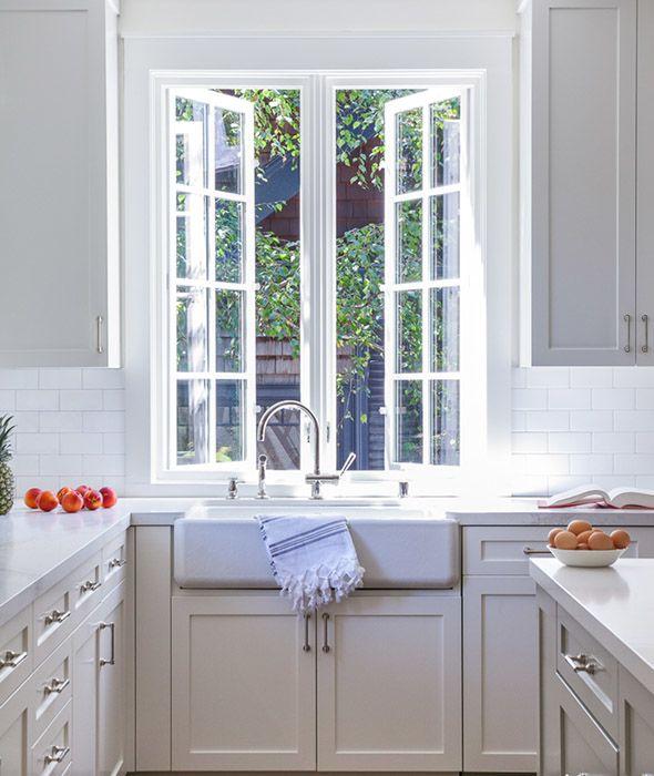 Lovely+kitchen+features+a+farmhouse+sink+and+a+gooseneck+faucet+under+push+out+casement+windows.