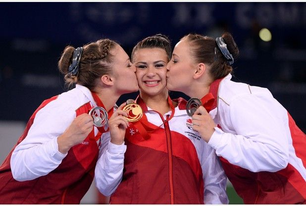 Gold medal winner Claudia Fragapane is kissed by fellow medallists Ruby Harrold, left, and Hannah Whelan -  individual all-around competition