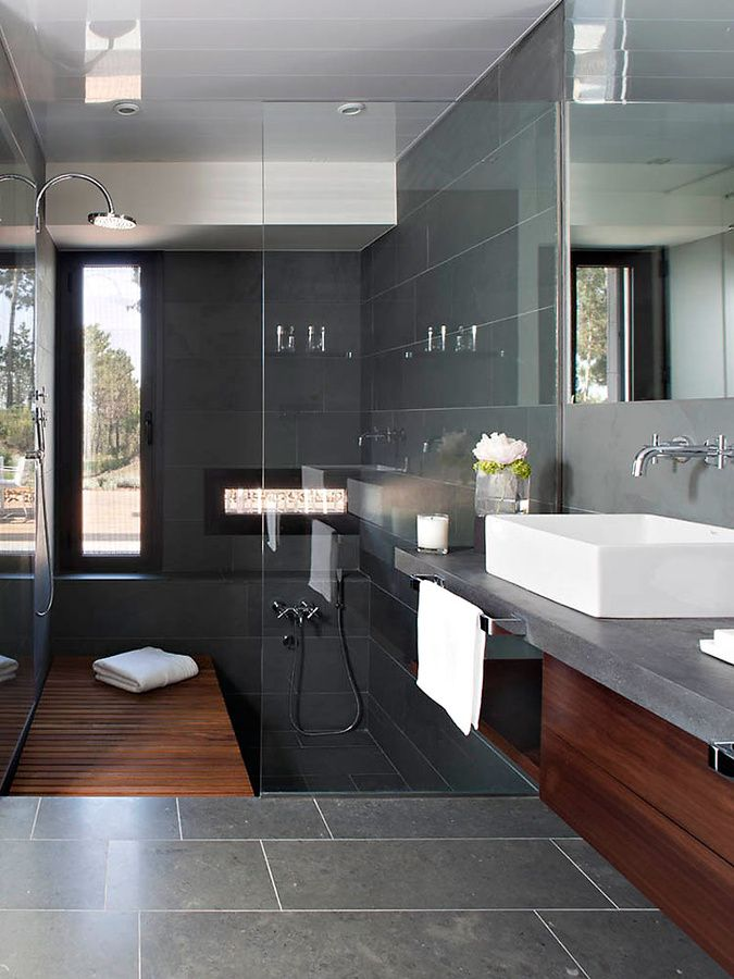 I like the monochromatic grey floor, counter, back splash, shower tile, along with the warm wood accents.