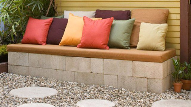 DIY Concrete Patio Bench for $30  If you're looking to increase your backyard entertaining space on a budget consider making this concrete patio bench. You'll put together the sides with concrete blocks and the top is a wooden plank covered with scrap foam padding and outdoor fabric.
