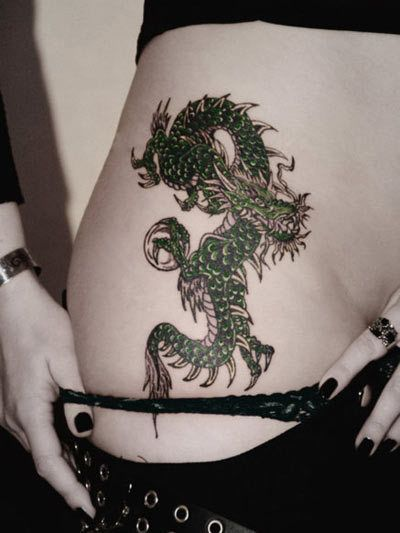 spiked dragon tattoo  too small and too high up, but otherwise similar placement.   Also, I prefer either a zigzag body, or if there is a complete wrap around for it to be closer towards the tail