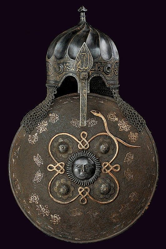 Ottoman 15th century style turban helmet and sipar (shield), 19th century. Helmet, blued,  pointed, twisted skull, the lower part engraved by floral motifs and cartouches, gold-inlaid inscriptions in Arabic, sliding nosepiece engraved and gold inlaid, butted  mail neck-defence. Sipar, a center sun shaped plaque with anthropomorphic face, and a relieved gilt decoration depicting a long snake woven around the four studs, the surface engraved with floral motifs featuring gold inlay.
