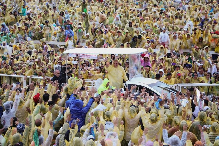 A sea of people surround Pope Francis as he passes by waving to pilgrims after holding a mass at Tacloban's airport on Jan. 17, 2015. An emotional Pope Francis, wearing a plastic poncho over his vestments to protect him from the wind and rain on Saturday, comforted survivors of Typhoon Haiyan, the Philippines' worst natural disaster that killed about 6,300 people 14 months ago.