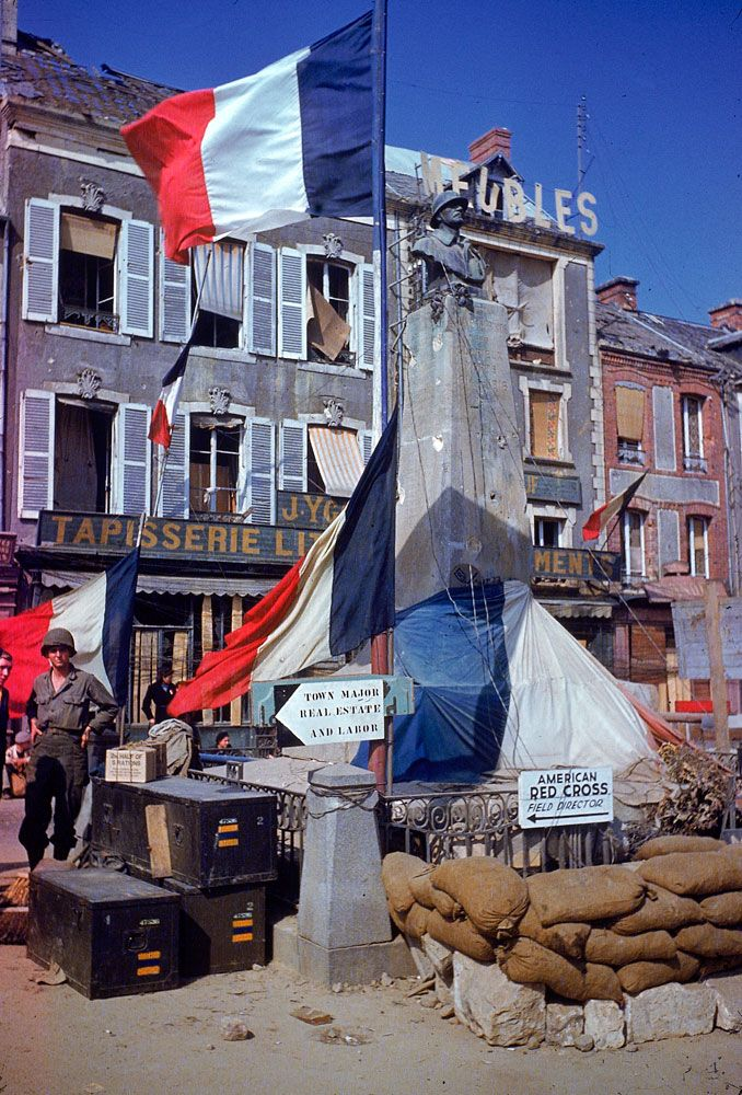 American troops stand beside a World War 1 monument bedecked with French flags after the town (exact location unknown) was liberated from German occupying forces, summer 1944. On the anniversary of D-Day, see Frank Scherschel's photographs from before and after D-Day in masterfully restored color: : http://ti.me/LrJMVr   (Frank Scherschel—Time & Life Pictures/Getty Images)
