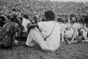 FESTAC 77à Lagos: la mémoire photographique de Marilyn Nance. Délégués américains (en blanc) discutant avec d'autres délégués dans le Stade National de Lagos pendant la cérémonie d'ouverture. Ils faisaient partie du National Black Theatre de Barbara Ann Teer, basé à New York.