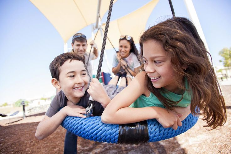 Photograph of smiling kids on a swing with parents in background. Outdoor family…