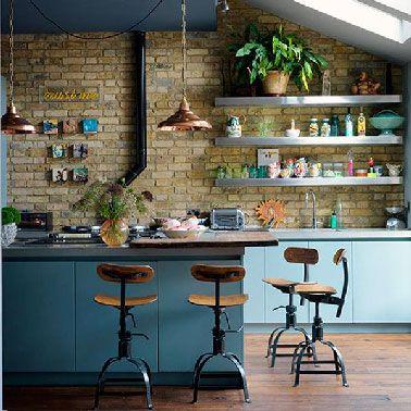 """Une cuisine style loft américain pimentée par des couleurs """"nature"""" : bleu, vert, jaune,une gammeparfaite sur un mur en pierre apparente plein de cachet."""