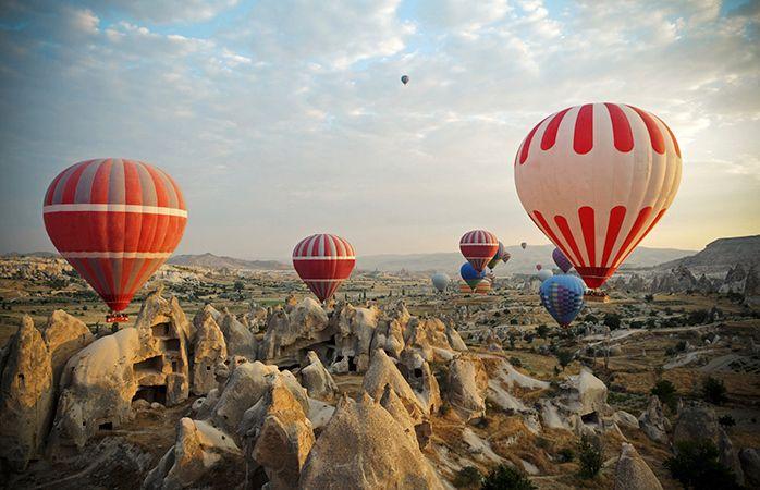 """Varmluftsballoner over Kappadokien, Tyrkiet. Varmluftsballoner over Kappadokien, Tyrkiet.  Du har helt sikkert set fotografier fra stedet, men intet pletskud yder Kappadokien retfærdighed. Kun en times kørsel fra byen, Kayseri, ligger dette forhistoriske kongedømme, som går 3.500 år tilbage i tiden. I dag imponerer stedets unikke hulemandsboliger og falliske vulkanske klippeformationer (også kendt som """"eventyrskorstene"""") en million besøgende hvert år.  Den bedste måde at opleve området på er…"""