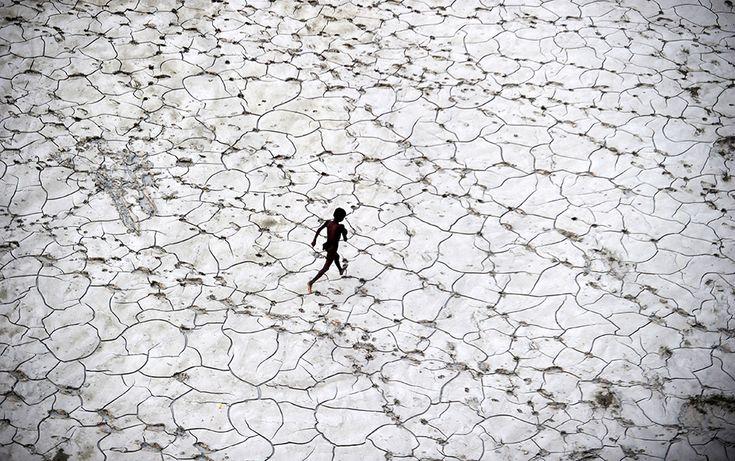 Un niño juega en el lecho de un río seco tras las inundaciones en Allahabad, India (Octubre 2013).- SANJAY KANOJIA (AFP)