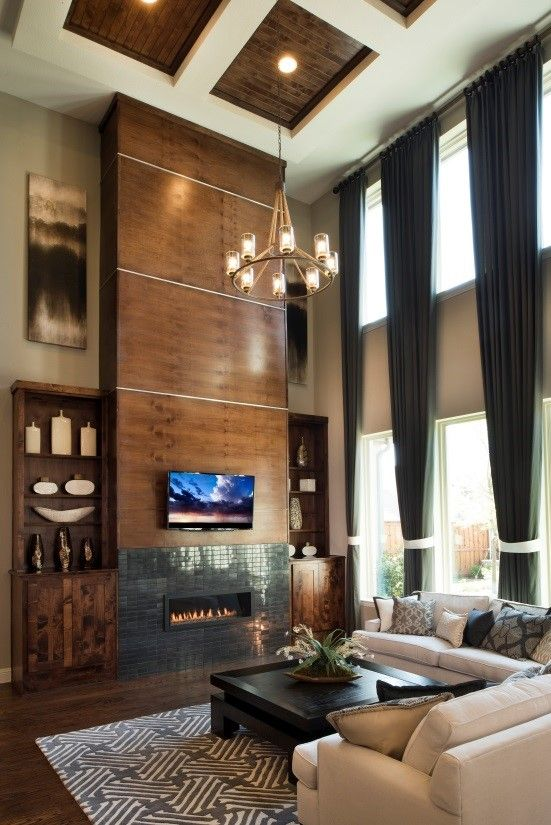 Two story family rooms give extra impact with floor to ceiling curtains, built-in wall units, and ceiling detailing. Seen in Trinity Falls, a Dallas community.
