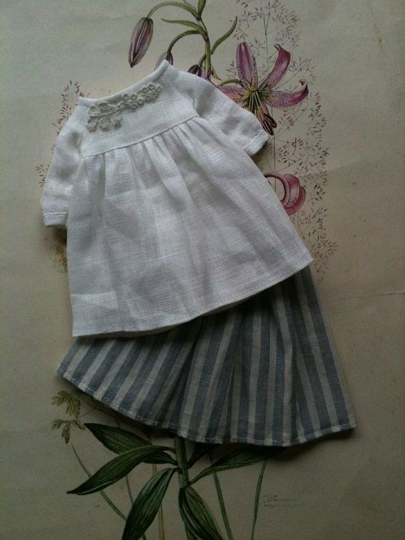 This dress has a pretty empire line bodice and gently puffed sleeves. The skirt`underneath is a striped cotton muslin in creamy white and greyish blue. The bodice of the dress has hand sewn lace appliqué details.