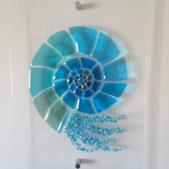 A Beautiful Fused Glass wall hanging of a Nautilus. The hanging is mounted on the wall with chrome fixings (Fixings supplied)  The picture is made by hand using transparent glass, and has copper inclusions in part of the shell. It is then fired in our kiln.  The hanging measures approximately 33cm x 43cm