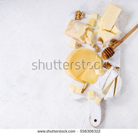 Cheese plate. Assortment of cheese with walnuts and honey from honey dipper on white wood serving board over white concrete texture background. Top view with space. Appetizer theme