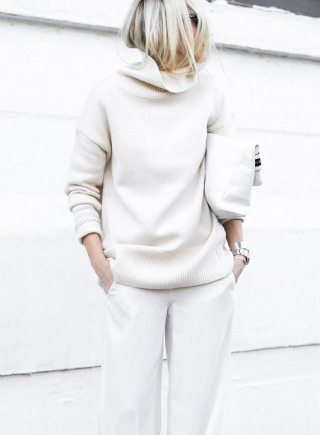 A white oversize turtleneck is paired with wide-leg jeans, a clutch, and stacked silver jewelry