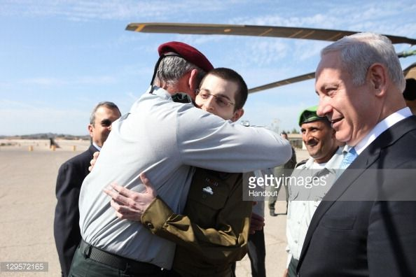 In this handout photo provided by the Israeli Defence Force, freed Israeli soldier Gilad Shalit is greeted by IDF Chief of General Staff Benny Gantz (R) at Tel Nof Airbase on October 18, 2011 in central Israel. Shalit was freed after being held captive for five years in Gaza by Hamas militants, in a deal which saw Israel releasing more than 1,000 Palestinian prisoners.