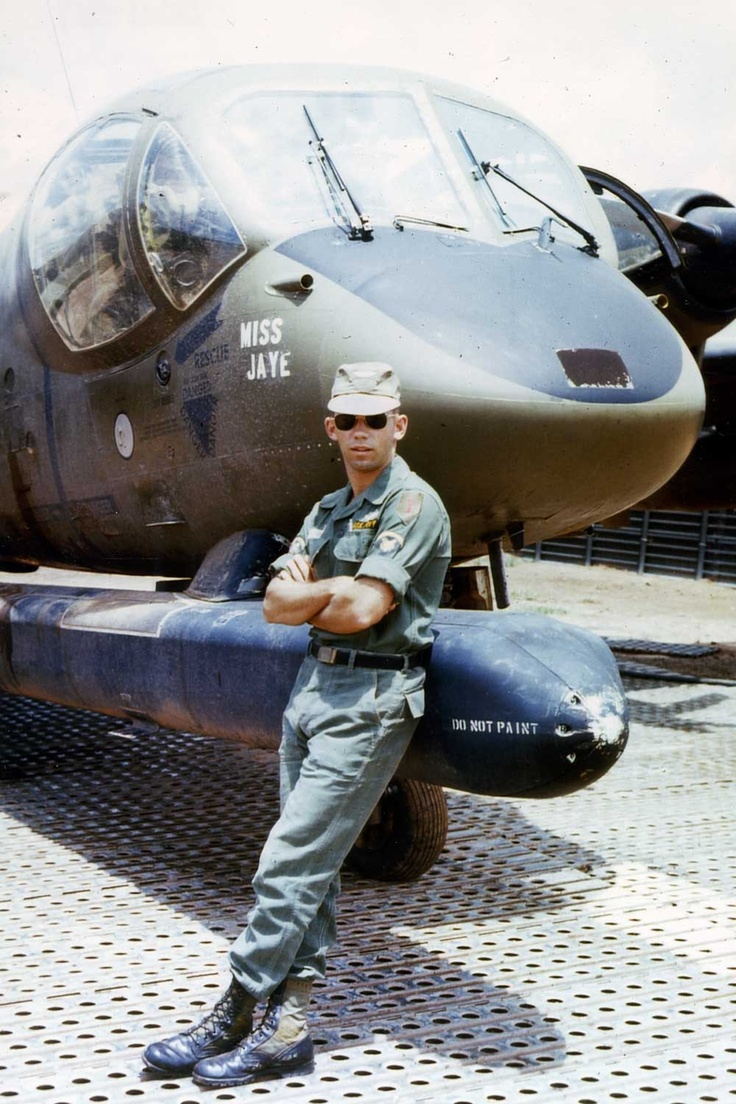 """Thomas Barnes spent 21 months serving in Vietnam as an operator/repairman of electronic equipment on the OV-1 aircraft. He liked his work so much, he voluntarily extended his enlistment. Throughout his tour, Barnes took hundreds of photographs, creating a unique record of his service. In this picture, Spec. Barnes shows off his new SP5 """"stripes"""" shortly after he sewed on the new rank. He is standing next to one of the OV-1 B-model Mohawks."""
