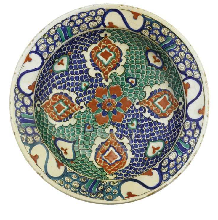 AN IZNIK POLYCHROME POTTERY DISH, TURKEY, CIRCA 1575 of shallow round form with an everted rim, decorated in underglaze cobalt blue, green and relief red with black outlines, with a central flowerhead in the cavetto and four stylised palmettes on a a fish-scale design, the rim with a broken wave pattern interspersed by S-shaped motifs, the reverse with flowerheads and foliate bouquets