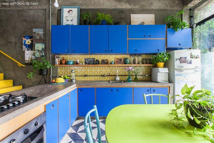 Cozinha super colorida tem parede de cimento queimado, armários na cor azul, azulejos estampados em amarelo e piso de ladrilho hidráulico.