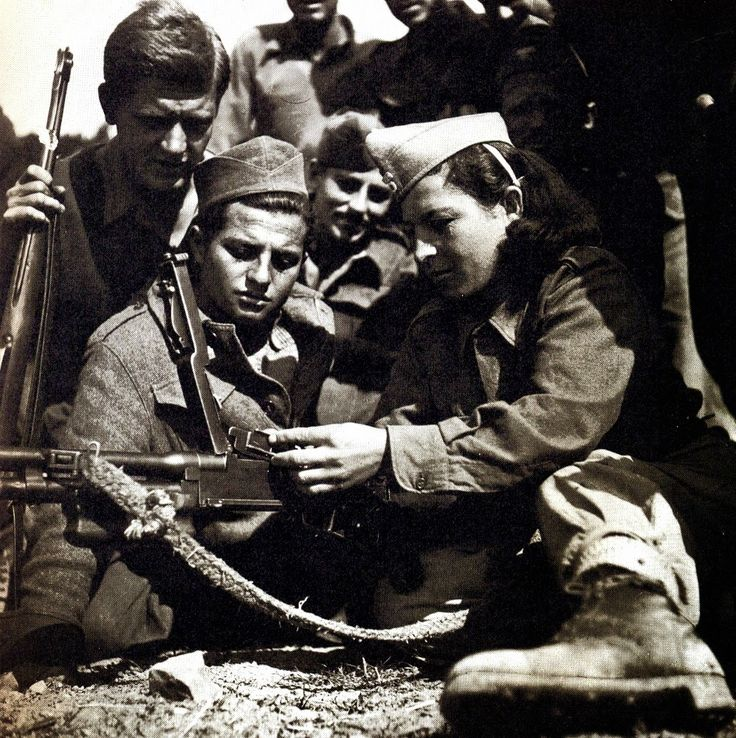 WW2 Greek Resistance: Female communist fighter teaches new recruits how to use automatic weapons. The communist resistance group ELAS included a good number of women.
