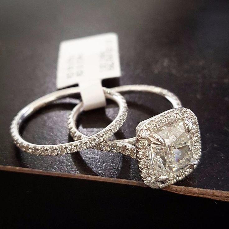 A simple cushion-cut diamond halo engagement ring looks classic when paired with a thin diamond eternity band.