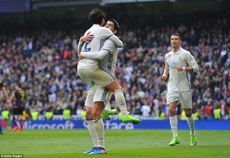 Isco jumps into the arms of Morata as the pair celebrate their hand in the goal, while Ronaldo jogs over to join the duo