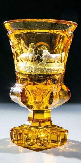 Pokal mit Pferden und ReiterNordböhmen, Schnitt August Böhm, um 1840 Farbloses, flächenfüllend mit Schäl- und Walzenschliff verziertes, bernsteinfarben lasiertes Glas.