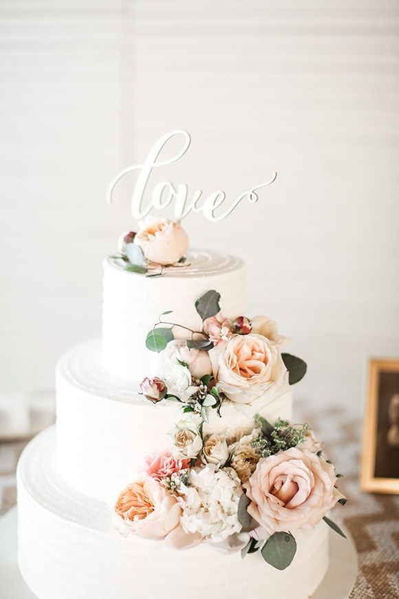 simple white, pretty cake draped in live flowers and greenery, topped with a personal laser cut topper