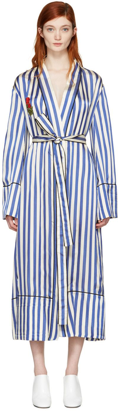 Long sleeve satin robe-style coat striped in blue and white. Silk piping in black throughout. V-neck collar. Embroidered graphic appliqué in red and green at bust and back. Detachable self-tie belt and welt pockets at waist. Tonal stitching.