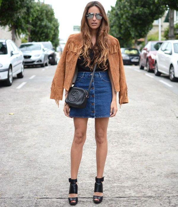 Street style com saia jeans de botões e jaqueta de suede e franjas.