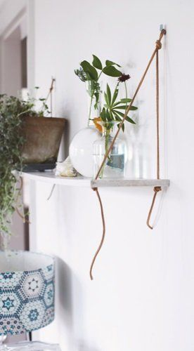 A simple and nice DIY shelf , decorated with plants and vases.  TIP Make your own shelf with leather straps and a board. Drill holes in a wooden shelf , run leather cord through the holes and tie it . Make sure to tighten the knots well .