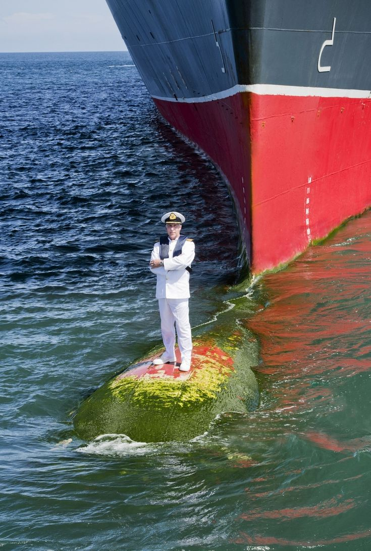 Captain Kevin Oprey on the bulbous bow of the Queen Mary 2 (QMII) cruise liner's 10th anniversary. The shoot took place at a port off the coast of Bali with two safety boats positioned nearby just in case.  Photographer James Morgan.