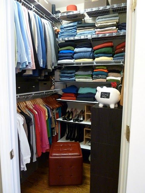 Small yet organized walk in closet. Store shoes in short bookcase with mirror above. Small hassock for sitting & storage.