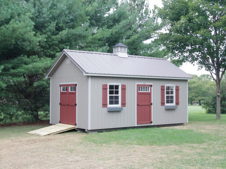 Portable storage building with a cupola in a backyard.