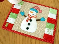 The Snowman Mug Rug gets a change of attire with a bobble hat and mittens.