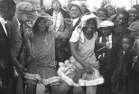 """'They call us baby dolls, so let's be red hot,' ... from a film strip via Story Sloan Gallery shows women dressed as """"baby dolls"""" dancing in New Orleans at Mardi Gras in 1931. The style soon spread to respectable black neighborhoods and is seeing a modern revival"""