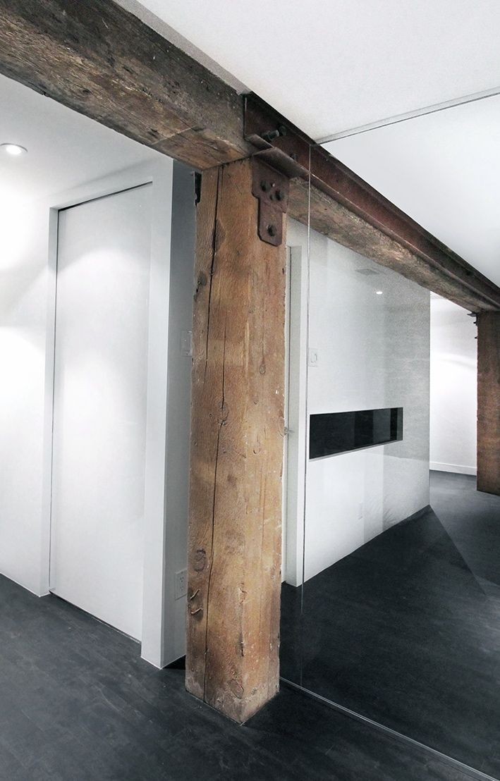 Rustic and contemporary mix - old beams with modern flooring, glass partition and wall finishes