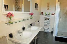 Ruime, comfortabele en lichte badkamer, dubbele wastafel, grote douche en eigen toilet