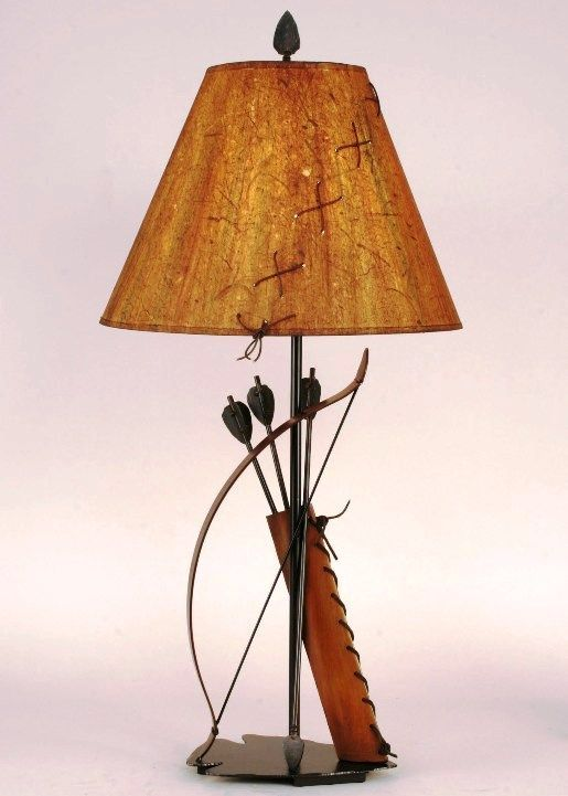 Bow Arrows and Quiver Metal Table Lamp with Shade 31.5in (CL12-R46A) - Perfect for the Southwestern style home, this 31.5 inch table lamp is composed of hand cut steel arrows, bow, and genuine leather laced quiver to create a great looking lighting source for your home. Comes with a rustic wood chip over parchment lampshade with leather lacing for a rustic look and topped with an arrowhead shaped finial. Base measures 12 x 9. Shade size is 7 x 16 x 12. Three-way socket. 100 watt Max bulb ...