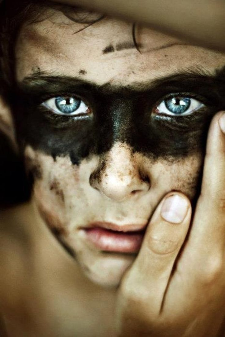 What is it that you see in his eyes? Blue eyed man with black paint on face.